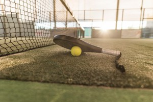 Paddle tennis image of outdoors court, racket, net and ball